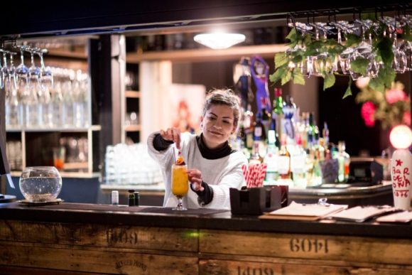A woman mixing a cocktail at a bar