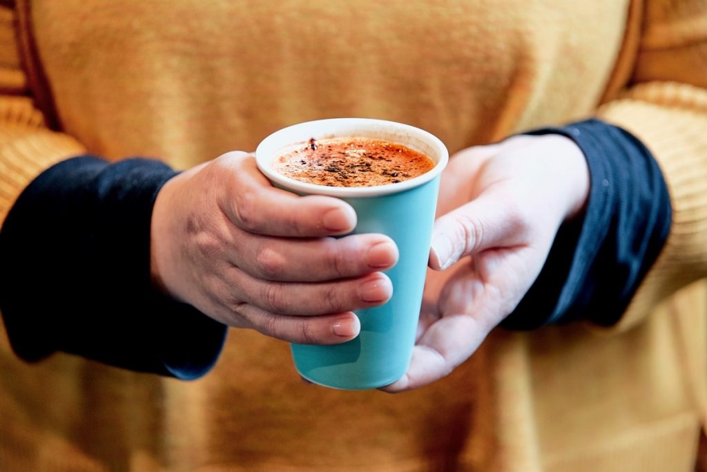 A hand holding a hot chocolate in a paper cup