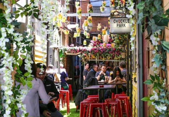 A laneway bar with hanging green plants and flowers