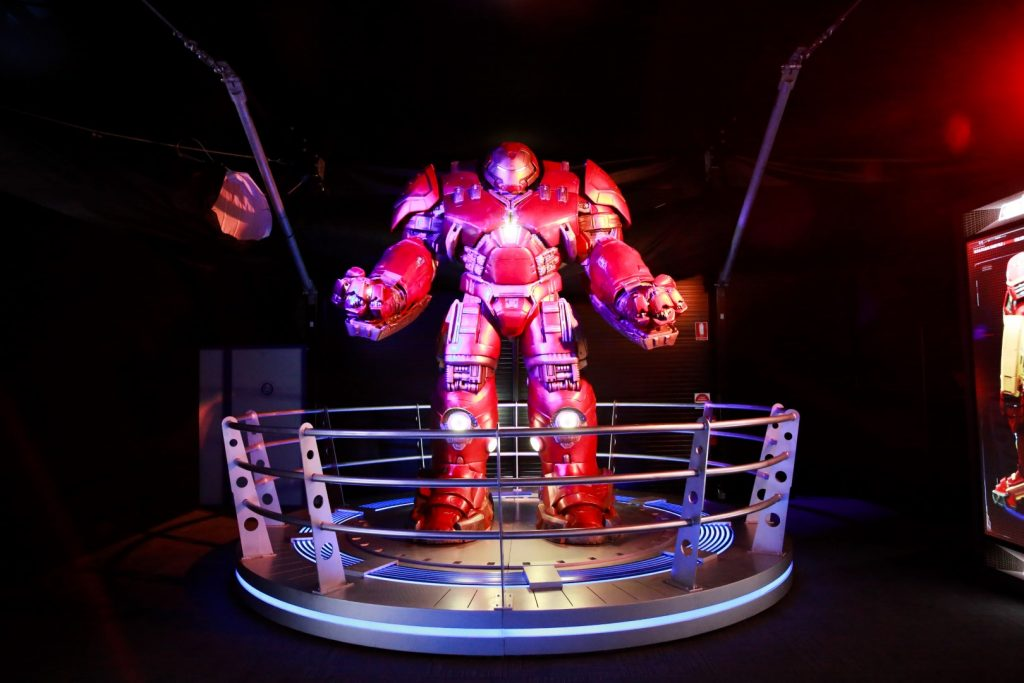 Dark room with giant red transformer character on display surrounding by silver railings.