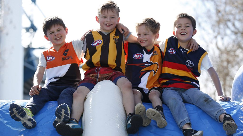 Four young boys sitting on inflatable slide dressed in their AFL team colours.