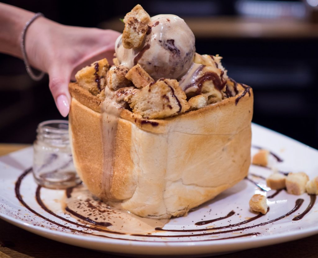 A carved out loaf of bread, filled with ice cream on a plate drizzled with melted chocolate.