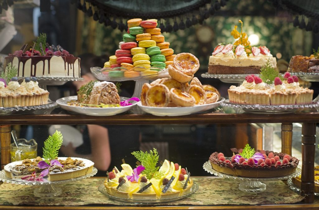 A window display featuring a plate of macarons, cakes and other baked goods