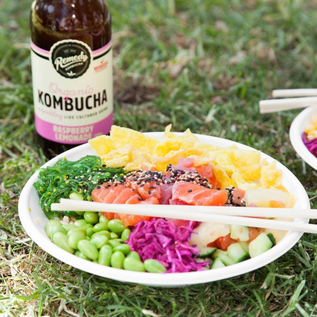 A bowl of fish and salad with a drink in a bottle, sitting on some grass