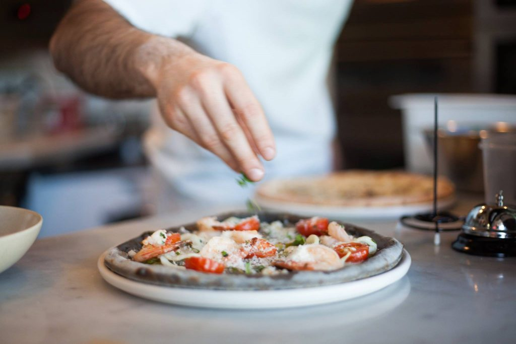 A hand adding topping to a pizza