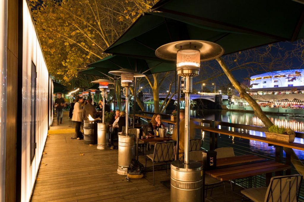 A restaurant overlooking the river with a wooden deck and big heaters