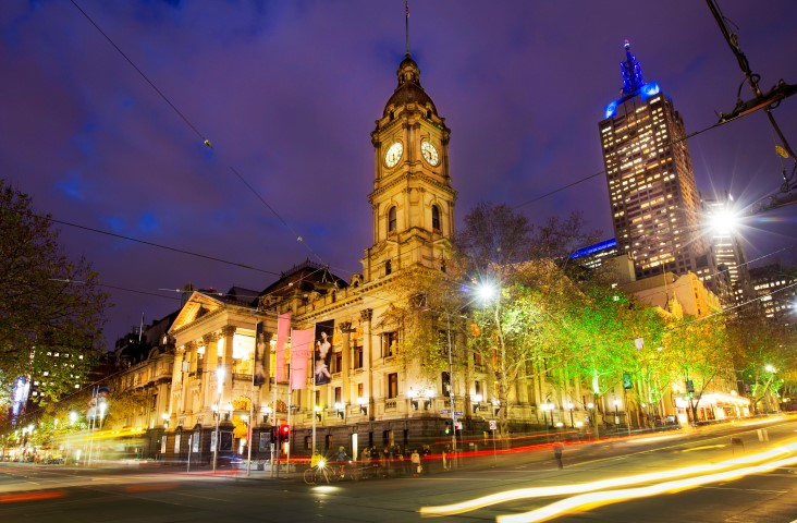 A night time shot of a large heritage building on the corner of two streets
