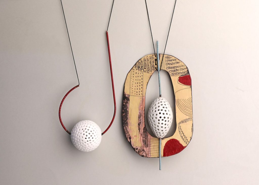 Two contemporary hand-crafted necklaces hanging on a wall