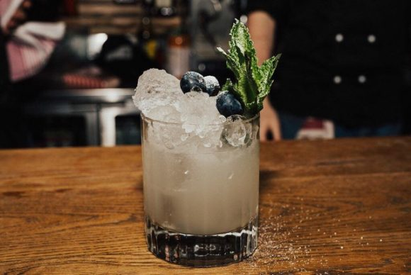 An icy cocktail topped with blueberries on a bar.
