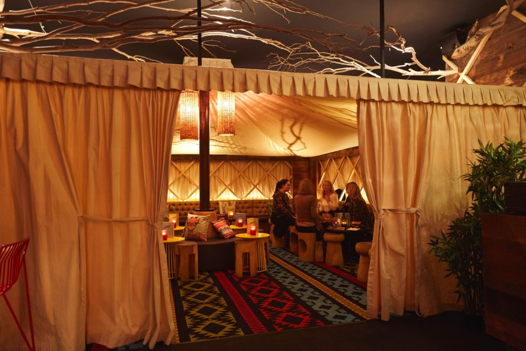 People drinking cocktails in an indoor tent set up in a bar
