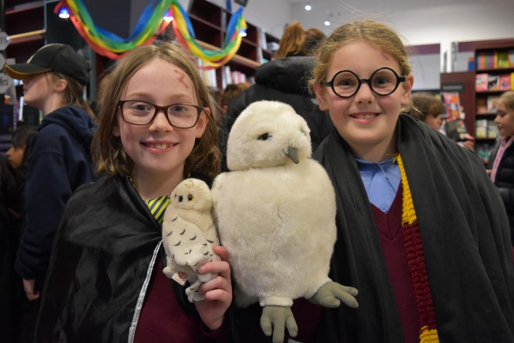 Two girls dressed as characters from Harry Potter, holding toy owls