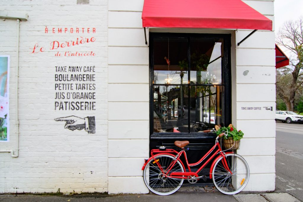 A bicycle leaning against the outside wall of a restaurant