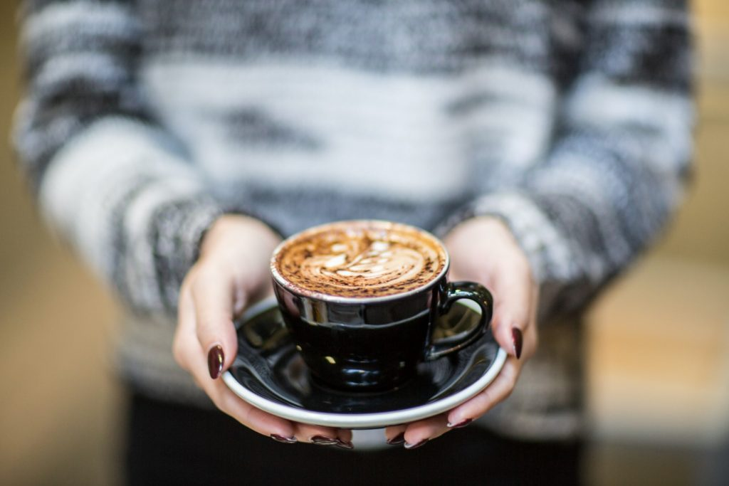 Hands holding a cappuccino