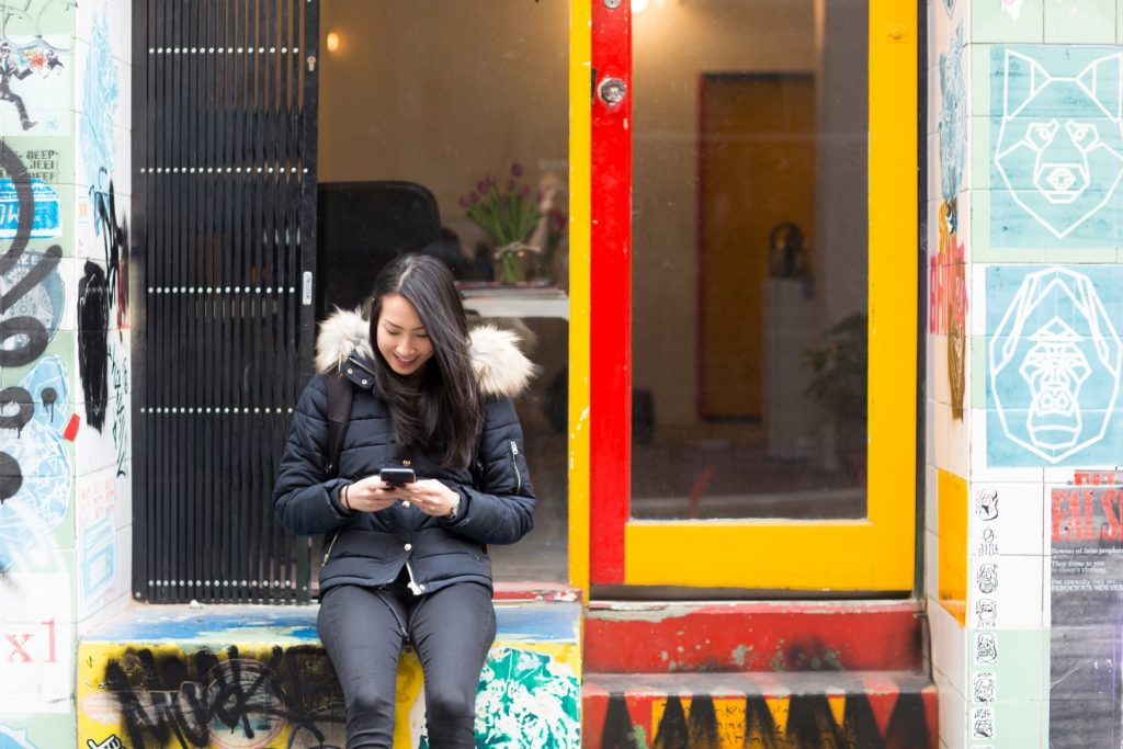 A girl sitting outside a shop looking at her phone