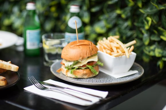 Burger and fries on a table against a leafy wall