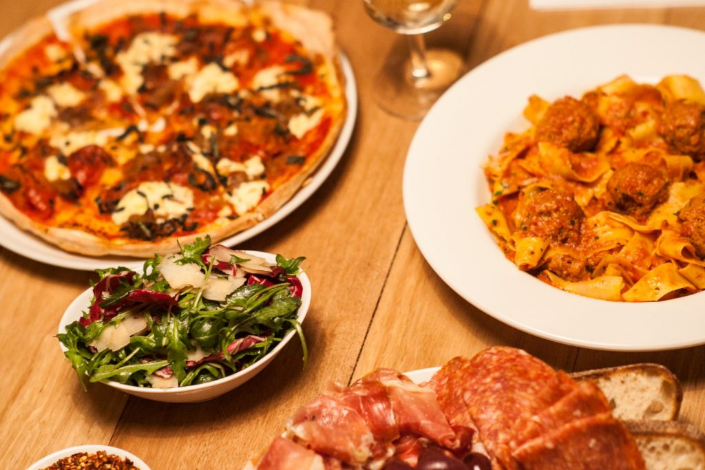 Two pizzas and salad on a table