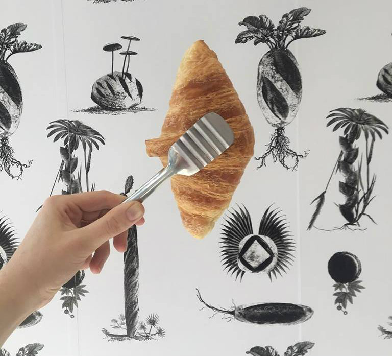 A hand holding a croissant with a pair of tongs