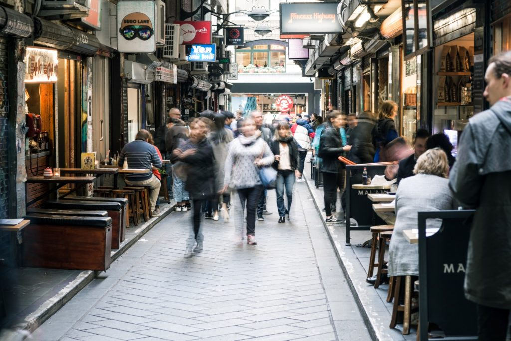 People walking down a busy city laneway