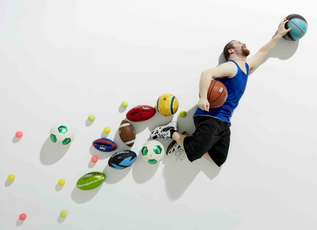 A man grabbing at a ball as he is jumping in the air. He is holding another ball under his arm with a trail of other balls behind him.