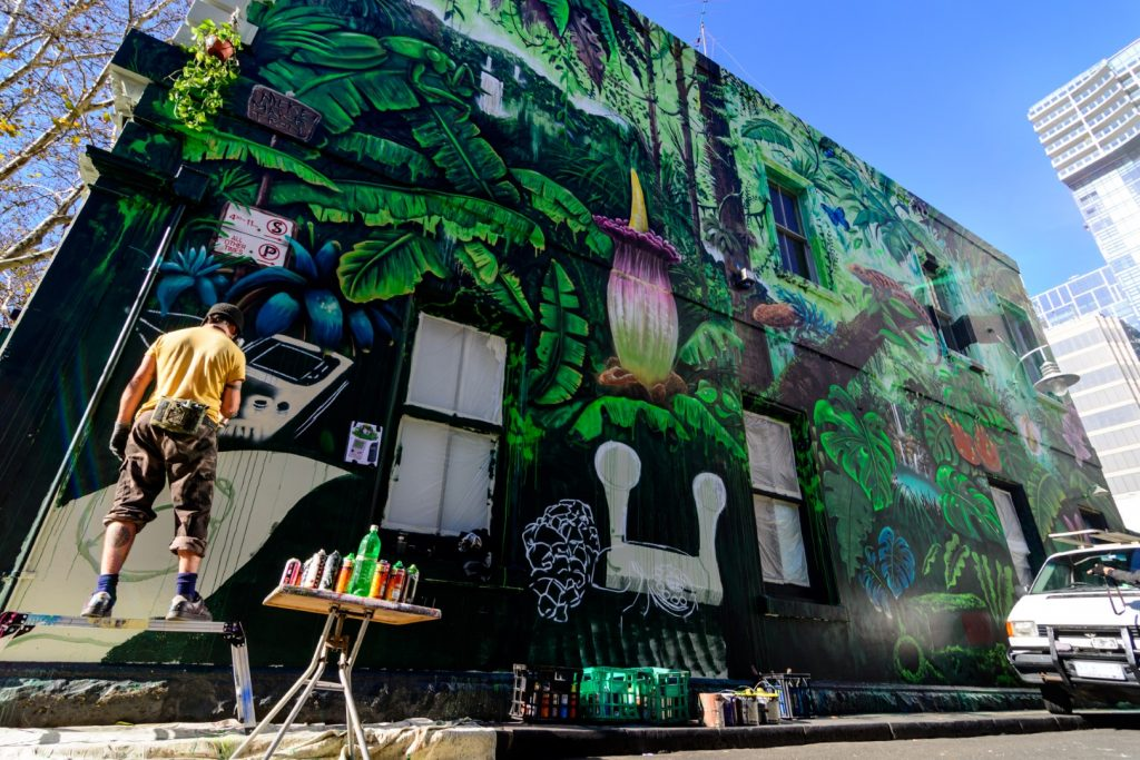 A man stands on a step and paints a mural on the side of a large building. The mural features a rainforest scene.