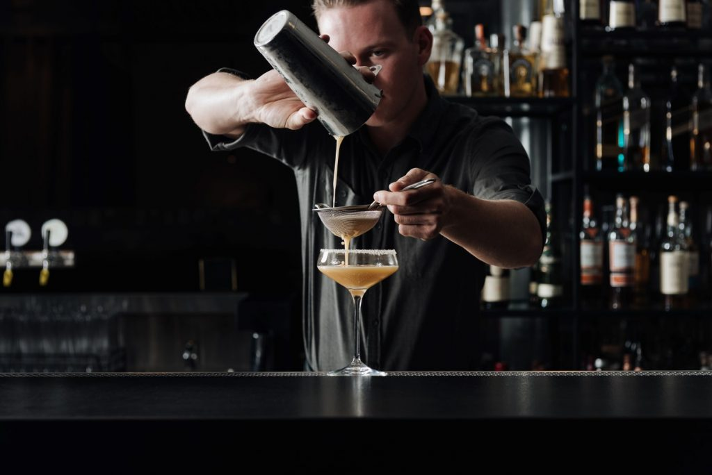 A bartender pouring liquid from a cocktail shaker through a strainer and into a glass