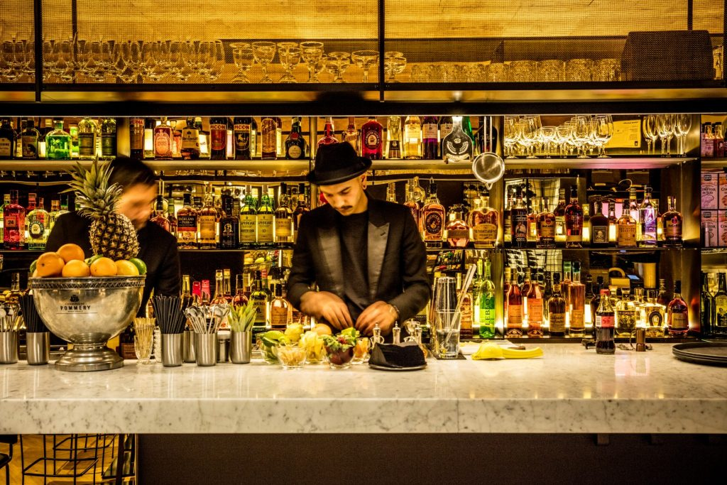 Two bartenders making cocktails in a bar