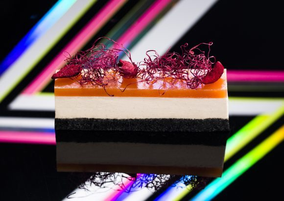 A layered licorice all sort cake with a colourful background.