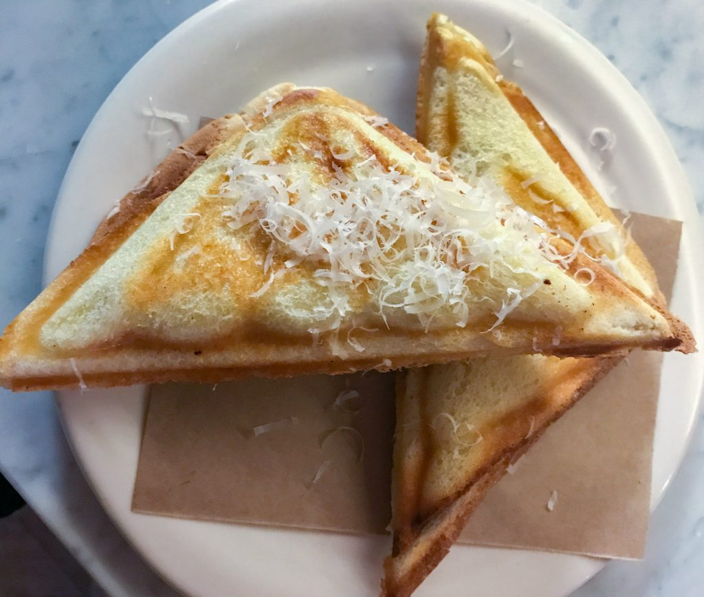 A toasted sandwich on a white plate, with grated parmesan cheese sprinkled on top