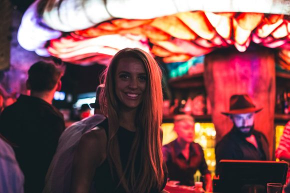 A woman in a crowded bar standing in front of a light shaped like a mushroom
