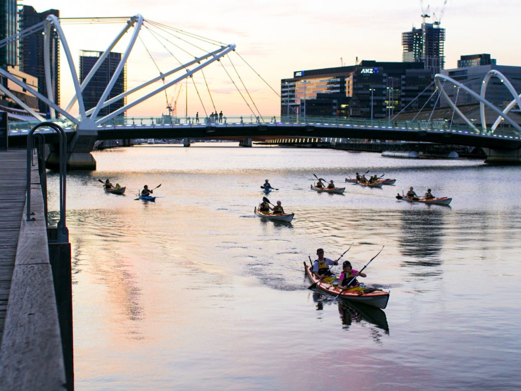 A group of people in kayaks travelling along the river in the middle of the city