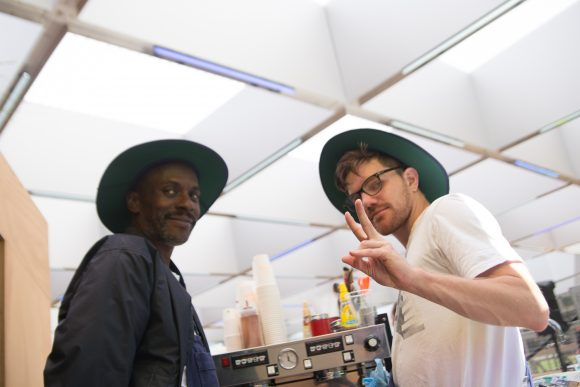 Tow guys wearing hats standing at a coffee machine