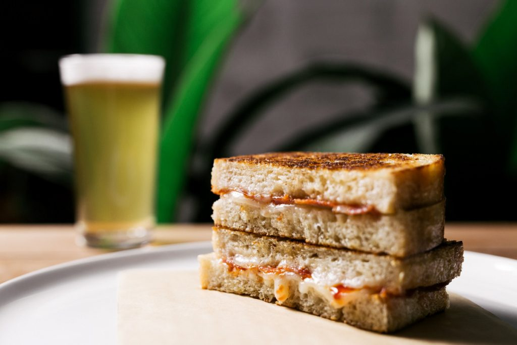 A toasted sandwich and a beer on a table