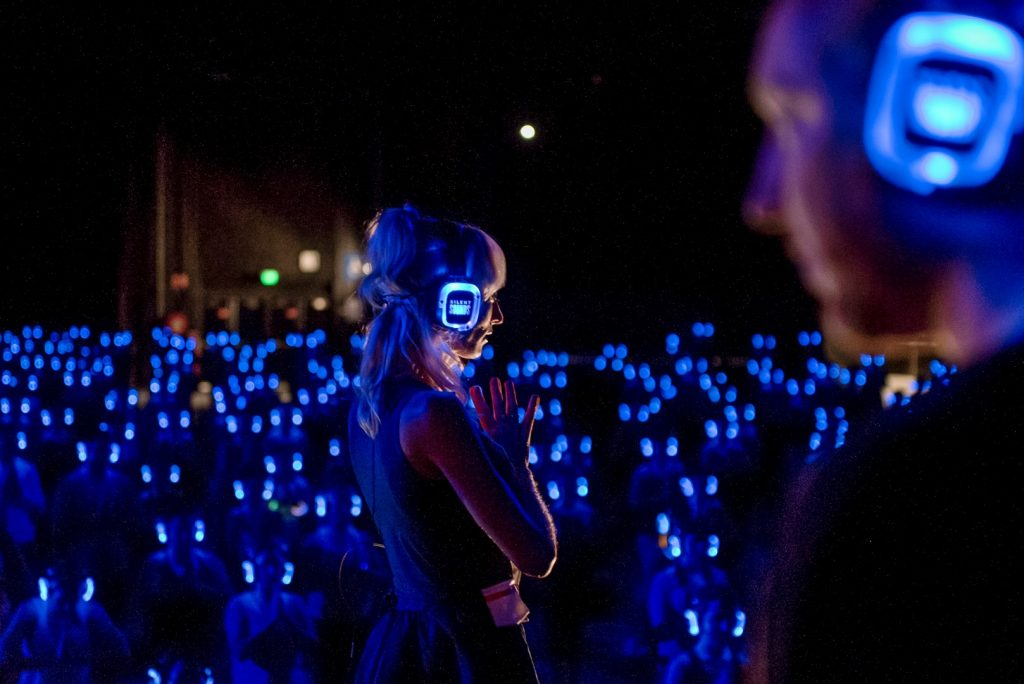 A woman standing in front of a group of people in a dark room with glowing headphones on