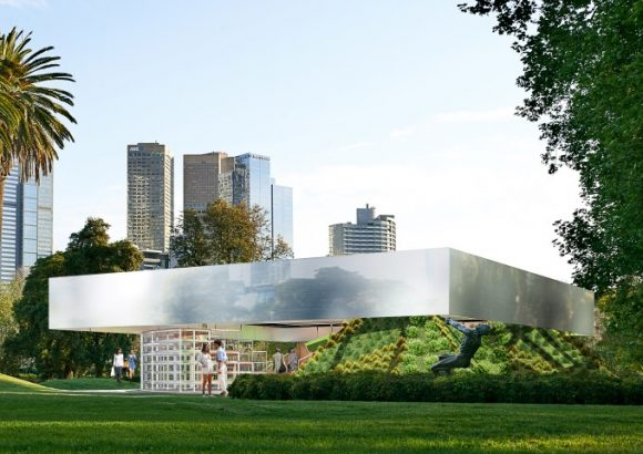 A modern temporary structure in a park with the city skyline in the background