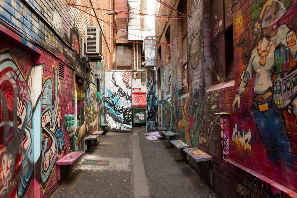 benches jutting out two walls in a street art covered laneway