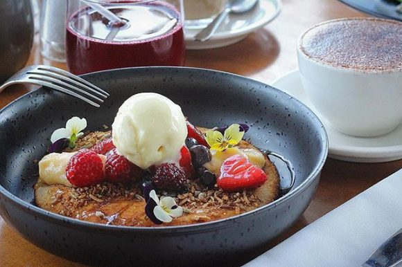 A bowl containing a pancake topped with fruit and icecream