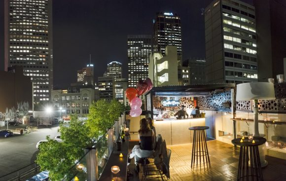 A rooftop bar with a view of the city skyline