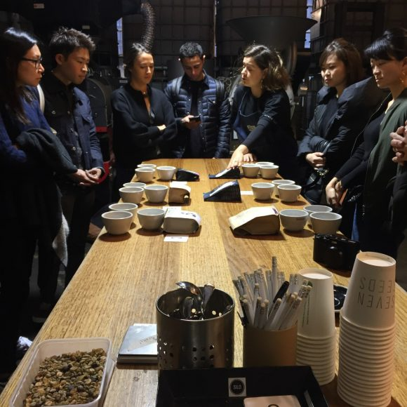 A group of people standing around a table about to taste different types of coffee
