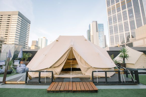 A luxury camping tent on the rooftop of a city building, with the city skyline in the background