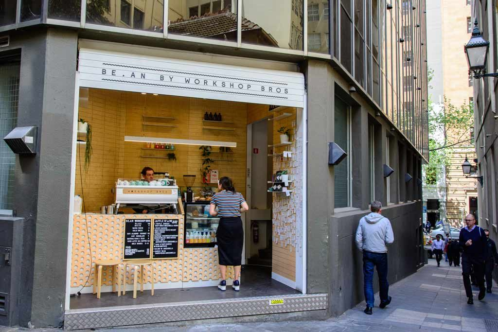 A small cafe in a laneway with a woman ordering a coffee