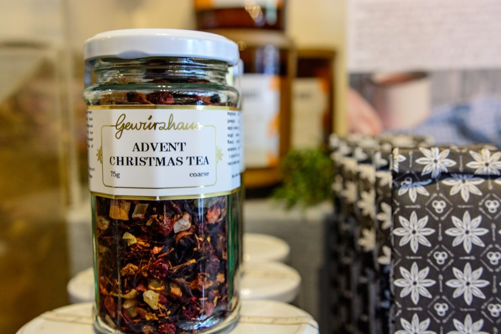 A clear glass jar filled with reddish brown tea leaves, with a white lid