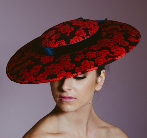 Woman wearing red and black floral patterned hat.