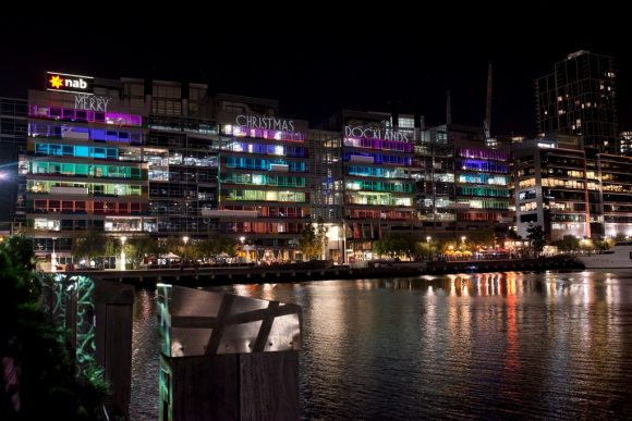 A series of modern buildings by the water lit up with colourful projections