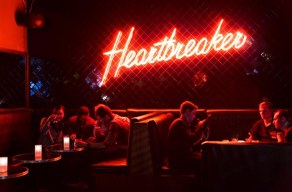 A red neon sign that says 'Heartbreaker' on the wall of a dark bar