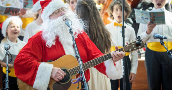 Santa Claus singing with a guitar at an outdoor concert.