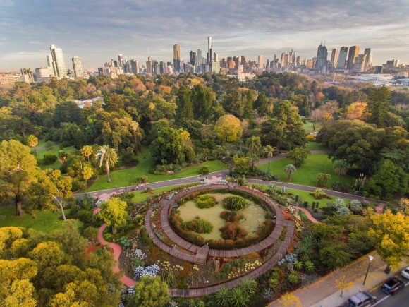 An aerial view of a huge landscaped garden with the city skyline in the background