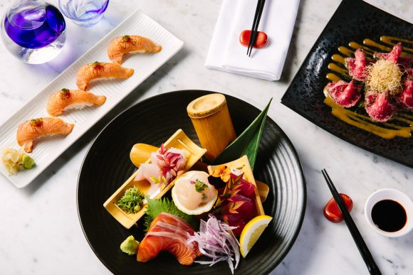 A black plate with japanese sashimi and sushi on it, on a white tablecloth