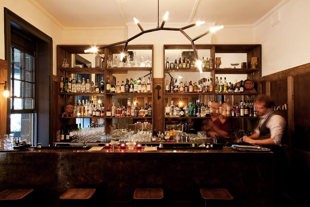 Two bartenders making cocktails in a bar with wooden furnishings