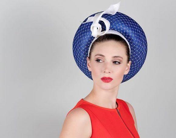 A woman wearing a race day blue hat