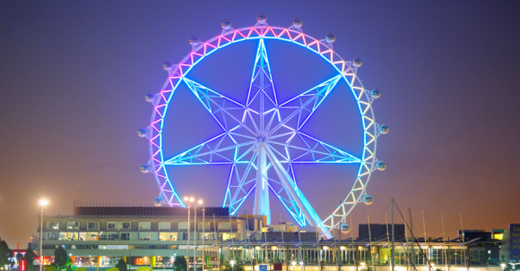 A ferris wheel lit up with colourful lighting